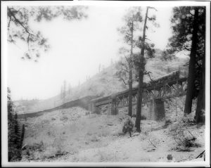 Train_passing_through_a_railroad_snow_shed_and_onto_a_tressel_in_the_mountains_at_Cisco,_ca.1910_(CHS-5030)